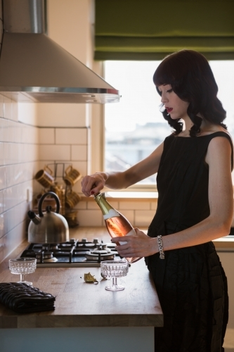 Young woman opening a bottle of pink champagne in the kitchen