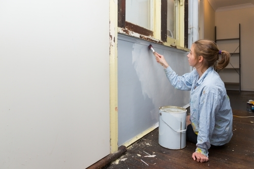 Young woman painting interior wall in old house
