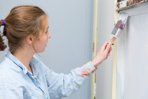 Young woman painting wall in old house