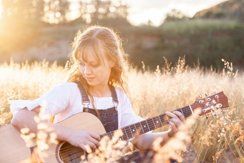 Young woman playing guitar in grass backlit by golden light