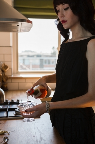 Young woman pouring a glass of pink champagne in the kitchen