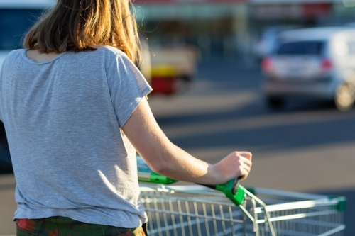 young woman pushing shopping trolley viewed from behind