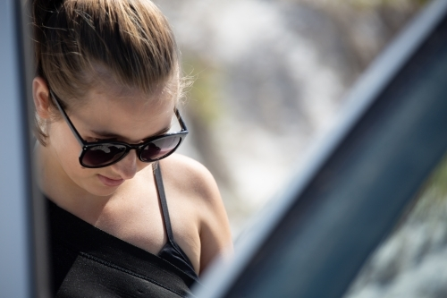Young woman seen through open door of car with sunglasses and hair tied back