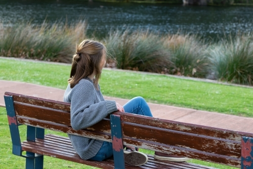 young woman sitting on park bench looking away from camera