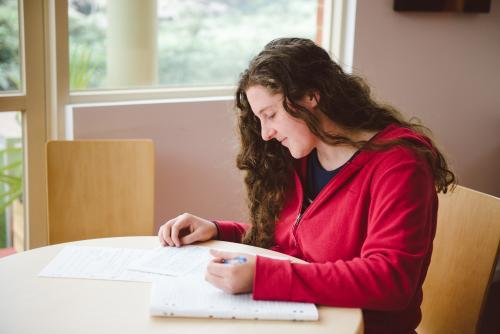 Young woman studying for a test and writing notes at university