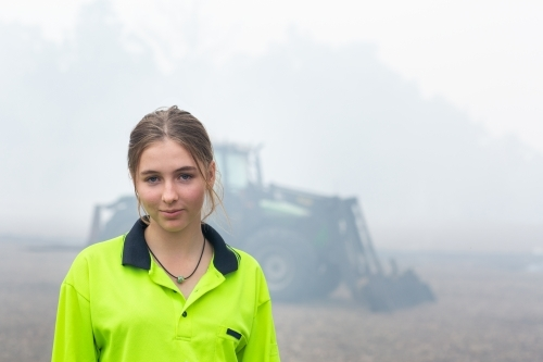Young woman wearing hi-vis in front of tractor