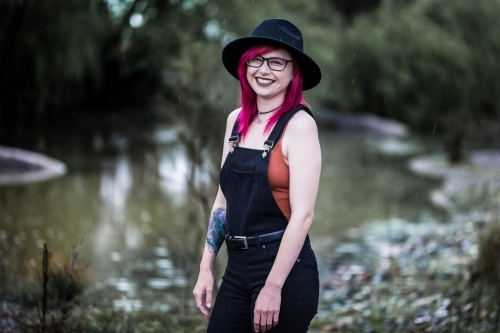 Young woman with coloured hair hat and glasses laughing near water
