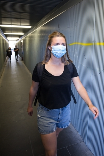 Young Woman with Face Mask Walking Through City Tunnel