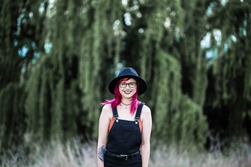 Young woman with pink hair smiling in front of willow tree