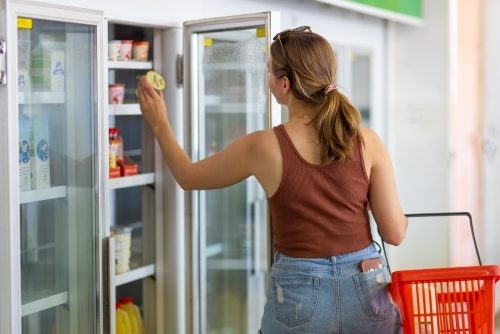 young woman with shopping basket taking yoghurt from shop refrigerator