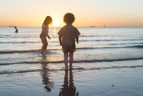Young boy and girl standing in the ocean at sunset