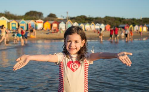 Young girl stands in the ocean with her arms outstretched