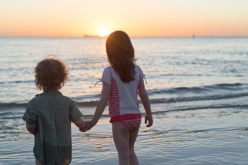 Young boy and girl at the beach holding hands watching the sunset