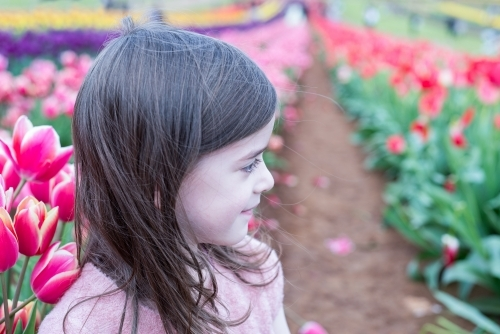 Young smiling girl looking at a tulip field