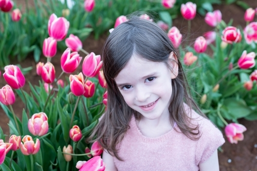 Smiling young girl looking up at camera from in a field of tulips