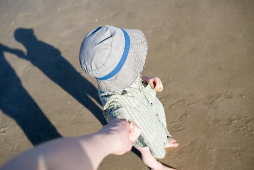 Young boy wearing a hat at the beach and holding hands seen from adult's POV
