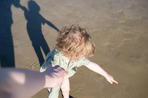 Young boy at the beach pointing and holding hands from adults POV