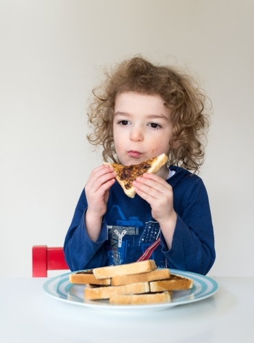 Young boy sitting at home eating sliced bread with vegemite