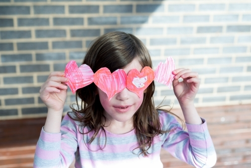 Young girl holding hand made cut out paper hearts over her eyes