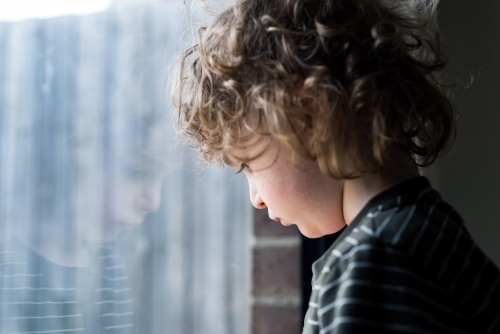 Young boy leaning his head against a window with his reflection