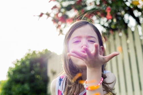 Young girl blowing orange flower petals-7725