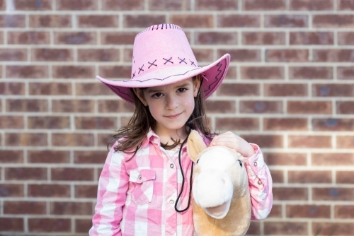 Young girl dressed as a cowgirl holding her hobby horse in the backyard