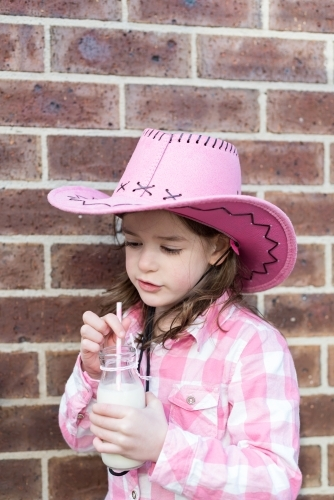 Young girl dressed as a cowgirl holding a milk bottle with a straw