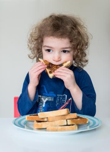 Young boy at home eating sliced bread with vegemite