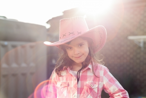 Young smiling kidl dressed as a cowgirl backlit with sunflare