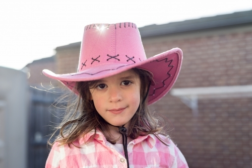 Young girl wearing a pink cowgirl hat and smiling