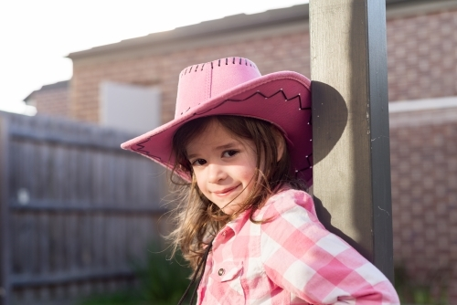 Young girl dressed as a cowgirl smiling and leaning against a post