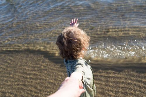 Young boy at the beach reaching out to the ocean, holding hands from adult's POV