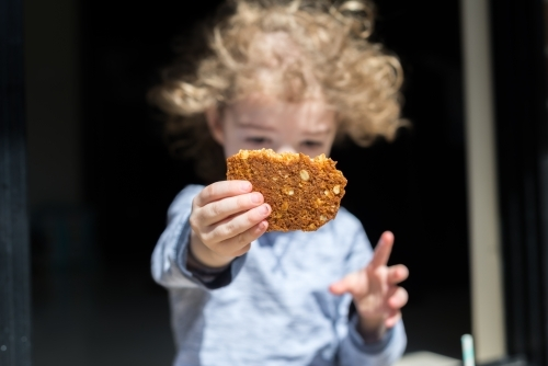 Young boy holding up a homemade ANZAC biscuit