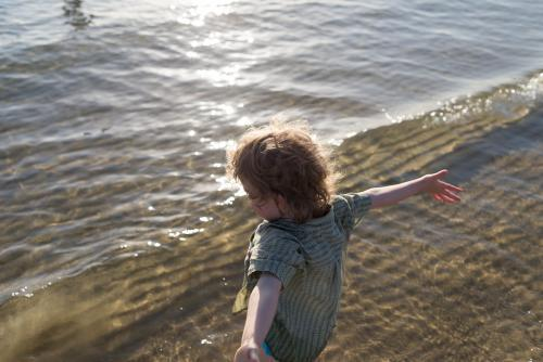 Young boy at the beach with arms outstretched standing in the ocean