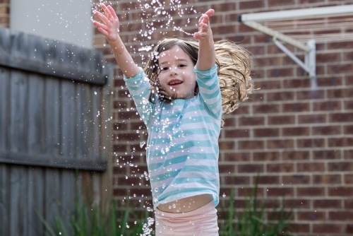 Young girl in the backyard splashing water