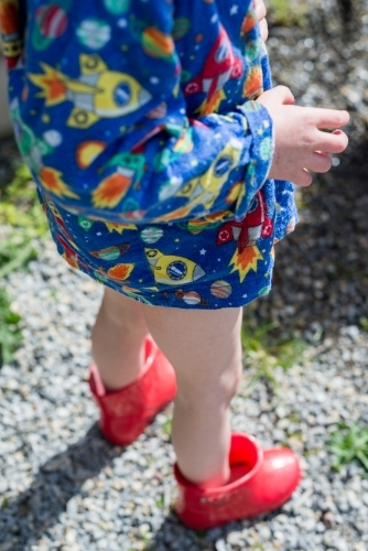 Young child wearing red gumboots and pyjama shirt