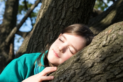 Young school girl sleeping in a tree