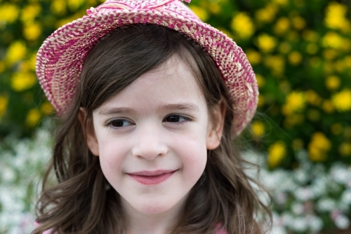 Young girl wearing a hat and smiling in the garden